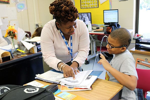 A Teacher of the Deaf, who is also an interpreter, works with a Deaf student in his classroom to learn his curriculum.