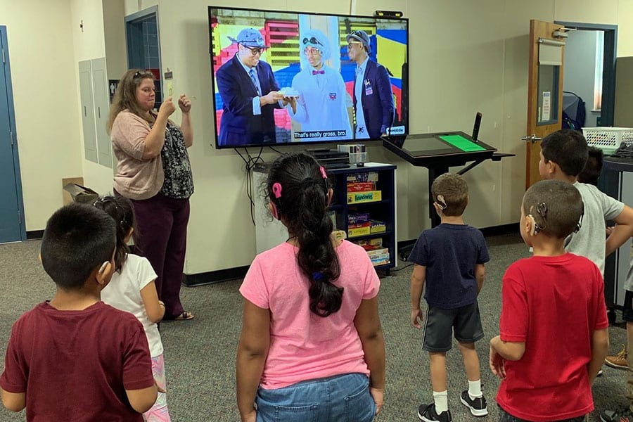 A small group of Deaf and hard of hearing students in the Bergen County Special Services School District face a large TV screen with a teacher next to it, and they dance and sign to the song.