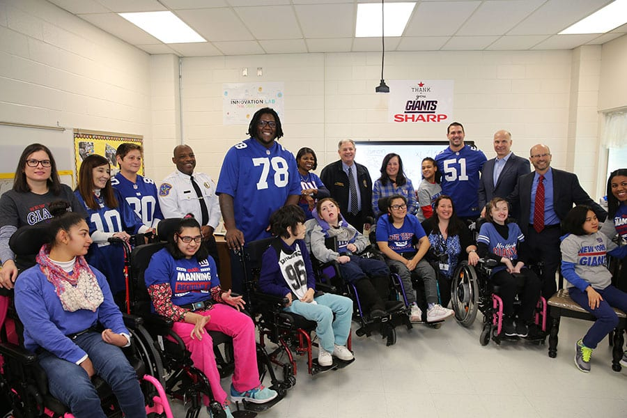 Members of the New York Giants football team pose with students and staff of the Bergen County Special Services School District's Bleshman Regional Day School after visiting the school.