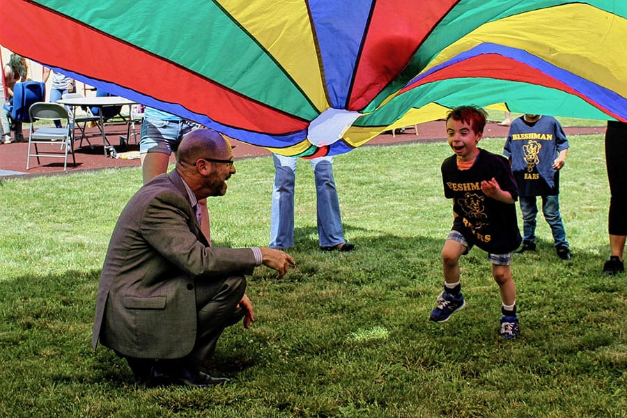 Bergen County Special Services School District Superintendent Dr. Howard Lerner sits under a parachute as a student in his district's Bleshman Regional Day School runs under it toward him.