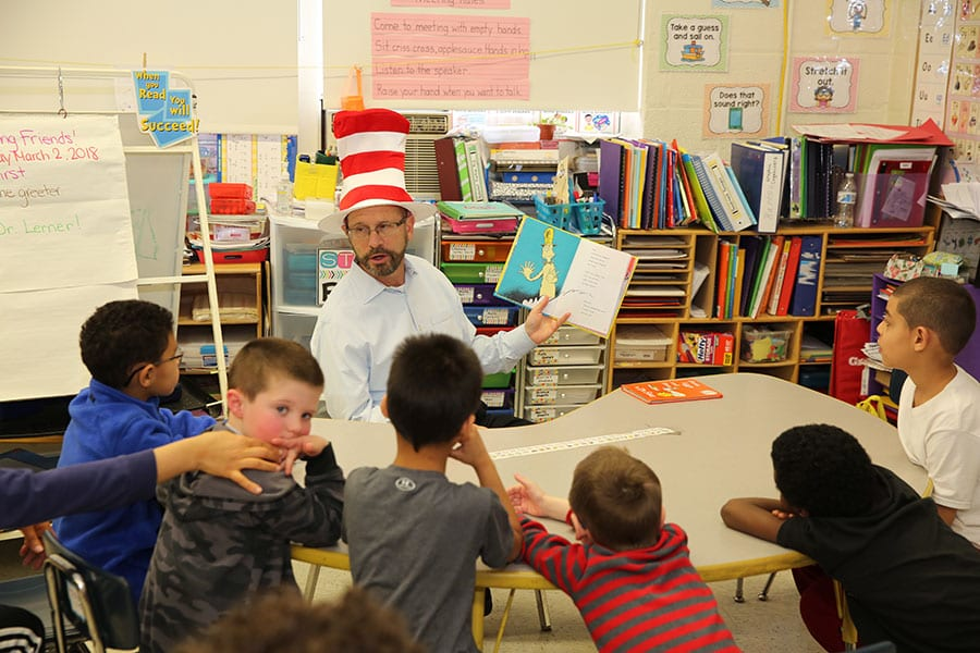 Bergen County Special Services School District Superintendent Dr. Howard Lerner reads to a small group of students at the Brownstone School while wearing the Cat in the Hat's striped hat.