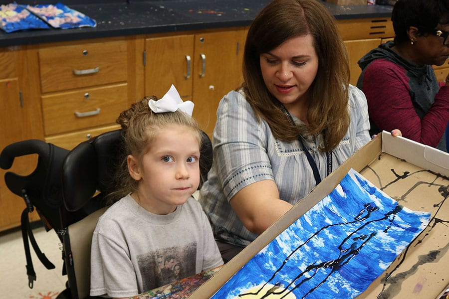 A Burlington County Special Services School District student in a wheelchair sits next to a staff member with a piece of art she created in front of her using a long sheet of paper and paint.