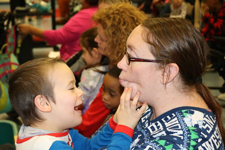 A young student in the Burlington County Special Services School District sits on a staff member's lap and playfully grabs her face.