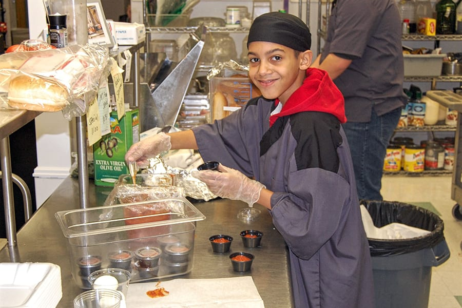 A student in the Cape May County Special Services School District smiles at the camera while prepping food