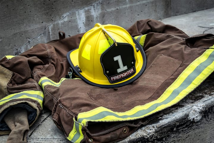 A Firefighter hat and coat lay on the ground