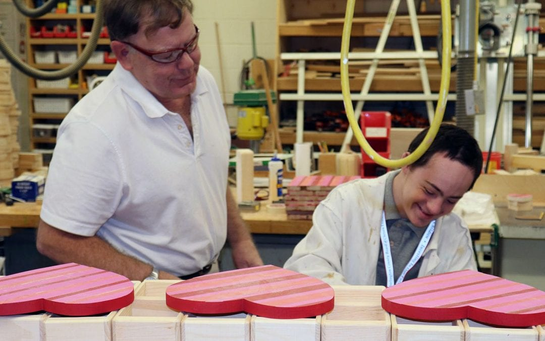 An instructor from Burlington County Special Services School District supervises a student as he paints wooden hearts as part of a wood shop project.