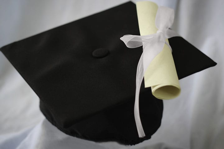 A scroll lays on top of a graduation cap