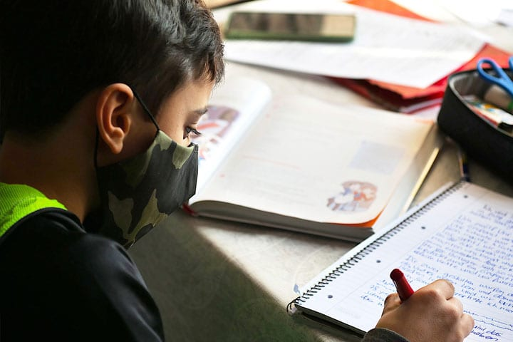 Student Writing with Mask on