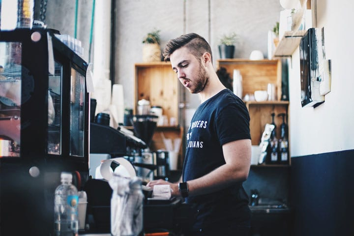 A young man works behind the counter in a coffee shop.