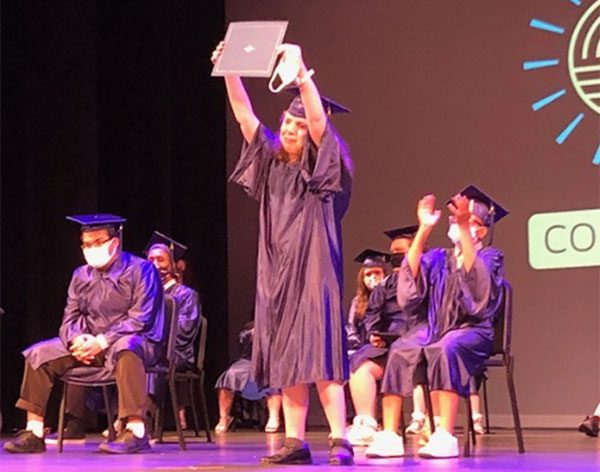 ACSSSD staff members assist a graduate on stage during the commencement ceremony.