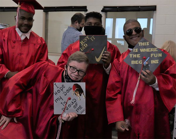 """BCSSSD graduates proudly hold up their decorated caps. One says, """"I hope my dog is proud of me"""" and another has the Nike swoosh and says, """"Just did it."""""""