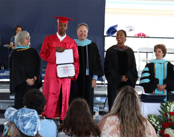 BCSSSD administrators smile behind a graduate on stage, who proudly displays his diploma during the commencement ceremony.