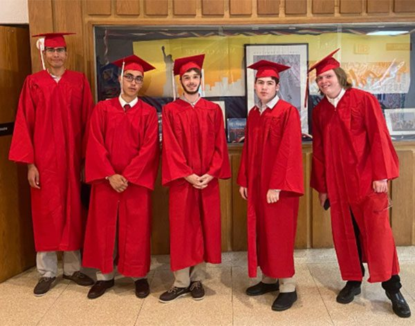 Members of the BCSSSD's Evergreen Program Class of 2021 gather together in a hallway prior to the graduation ceremony, wearing traditional caps and gowns.