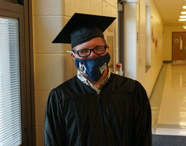 A proud GCSSSD graduate smiles behind his facemask in a hallway following the graduation ceremony.