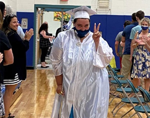 A GCSSSD graduate in a cap and gown puts up the peace sign as she walks during the graduation procession while the crowd claps in the background.