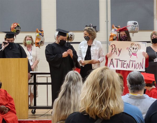 """Graduates and administrators at CMCSSSD gather on stage during the commencement ceremony. While one student addresses the crown, another holds up a sign that says """"pay attention"""" to remind those in the audience to be quiet and listen."""