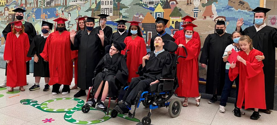 CMCSSSD graduates dressed in red and black caps and gowns gather together for a photo following the commencement ceremony, some are wearing masks, some are waving at the camera.